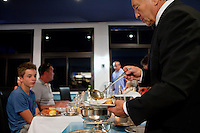 Jean Marchi, maître d'hôtel of restaurant 'Le Calypso', spoons broth over fish as he serves bouillabaisse to diners at Le Calypso, Marseille, France, 25 August 2012. Bouillabaisse is a traditional Provençal fish stew originating from Marseille.