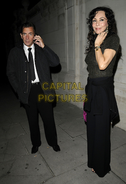 DUNCAN BANNATYNE & MARIE HELVIN.The Red Room Launch Party at Les Ambassadeurs Club, Mayfair, London, England..November 2nd 2009.full length black tie jacket banatyne trousers top talking on mobile phone hand.CAP/CAN.©Can Nguyen/Capital Pictures.