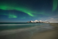 Northern Lights shine in sky over Storsandnes beach, Flakstadøy, Lofoten Islands, Norway