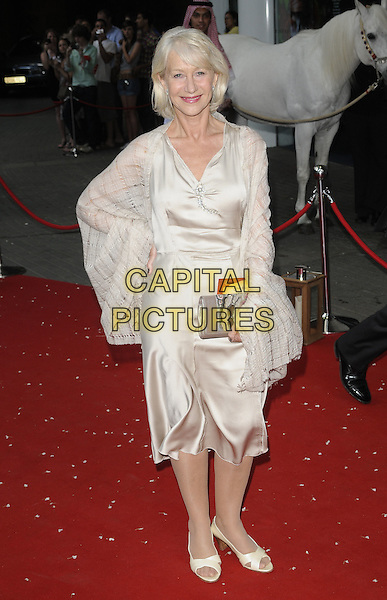 DAME HELEN MIRREN .Royal Film Premiere of 'Arabia 3D' at the BFI Imax cinema, Waterloo, London, England, UK, May 24th 2010 ..full length  cream dress wrap shawl open toe shoes silk satin hand on hip beige clutch bag .CAP/CAN.©Can Nguyen/Capital Pictures.