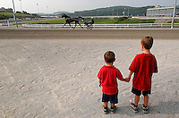 Two boys watch a horse warm up at a harness racing track