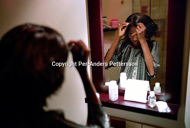 GABORONE, BOTSWANA - FEBRUARY 25: Elisabeth Ramolale, age 33, tries a wig in her room at the Metcourt Hotel, a day before the Miss HIV Stigma Free Botswana competition held annually in the international convention center on February 25, 2005 in Gaborone, Botswana. Elisabeth, a woman living with HIV, doesn?t take any antiretroviral drugs, as she believes that she can live a normal life without them. Elisabeth finished among the top five in the competition. The pageant is held to make the people of Botswana more aware of HIV-Aids, and stop the stigma that makes people afraid of being tested. Botswana has a population of about 1,7 million people and about 38 percent are believed to be infected with the virus..(Photo: Per-Anders Pettersson/Getty Images).