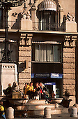 Budapest, Hungary. People (couple) sitting on steps of a fountain eating McDonald's food; Citibank cash machine behind.
