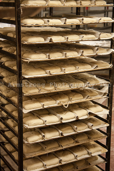 Unbaked loaves of bread in a rack of large trays at a bakery.