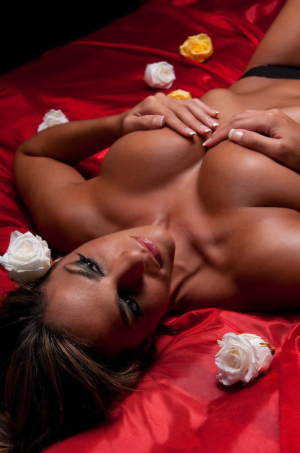 Young hispanic woman laying in bed with silk sheet and roses.