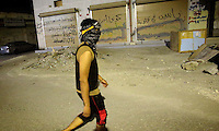 Photographer: Rick Findler..21.04.13 A young protester walks toward the front lines of a clash between police and protesters in Ma'ameer, Bahrain. The number of protests in Bahrain increase dramatically during the sporting event to help bring attention to the ruling bahraini Sunni royal family's many human rights abuses and repression of the country's Shiite people.