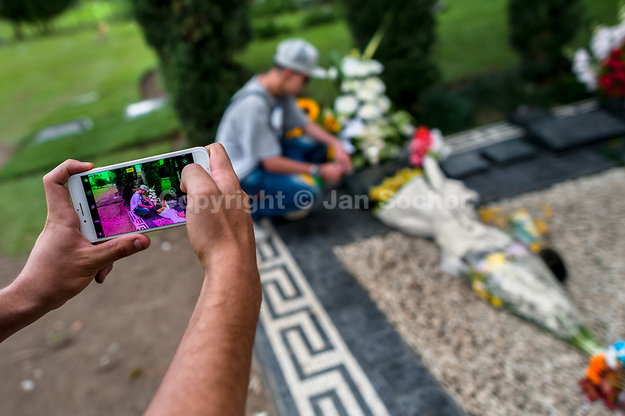 "A young Colombian man takes a snapshot of his friend while visiting the tomb of the drug lord Pablo Escobar at the cemetery of Montesacro, in Itagüí, Colombia, 2 December 2017. Twenty five years after Pablo Escobar's death, the legacy of the Medellín Cartel leader is alive and flourishing. Although many Colombians who lived through the decades of drug wars, assassinations, kidnappings, reject Pablo Escobar's cult and his celebrity status, there is a significant number of Colombians who admire him, worshipping the questionable ""Robin Hood"" image he had. Moreover, in the recent years, the popular ""Narcos"" TV series has inspired thousands of tourists to visit Medellín, creating a booming business for many but causing a controversial rise of narco-tourism."