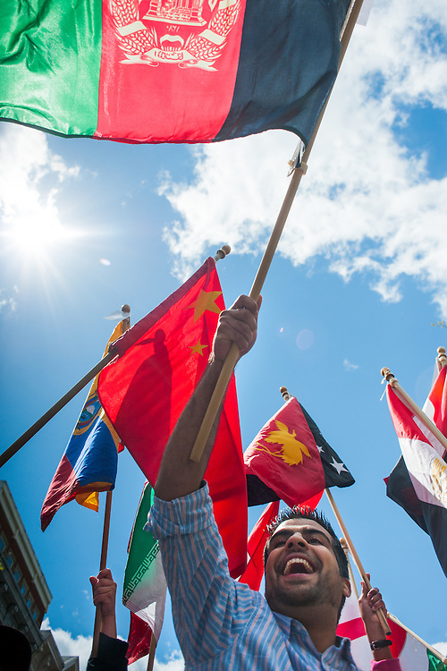 Students march down court street carrying flags in the international street fair parade. Photo by: Ross Brinkerhoff.