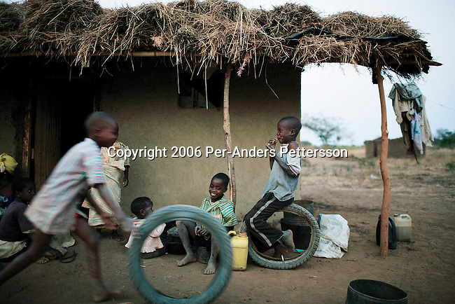 MPHANDULA, MALAWI - AUGUST 21: Unidentified boys play with tires outside the family house on August 21, 2006 in Mphandula village, about 30 miles outside Lilongwe, Malawi. Its one of the poorest families in the village and they are struggling to feed the family by working on nearby farms. Mphandula is a poor village in Malawi, without electricity or clean water. Nobody owns a car or a mobile phone. Most people live on farming. About 7000 people reside in the village and the chief estimates that there are about five-hundred orphans. Many has been affected by HIV/Aids and many of the children are orphaned. A foundation started by Madonna has decided to build an orphan center in the village through Consol Homes, a Malawi based organization. Raising Malawi is investing about 3 million dollars in the project and Madonna is scheduled to visit the village in October 2006. Malawi is a small landlocked country in Southern Africa without any natural resources. Many people are affected by the Aids epidemic. Malawi is one of the poorest countries in the world and has about 1 million orphaned children. (Photo by Per-Anders Pettersson)
