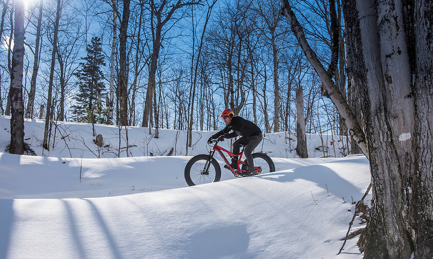 Riding the Eh Line jump trail in winter on fat bikes in Marquette, Michigan.