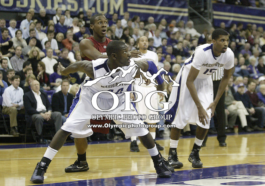 14 January 2010:  Washington Huskies #44 Darnell Gant (left) and #15 Scott Suggs (right) set up to block out against Stanford's #23 Gabriel Harris during a free throw. Washington won 94-61over Stanford at the Bank of America Arena in Seattle, WA.