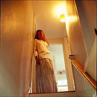 Girl, side lit by hallway light, standing at the top of the stairs