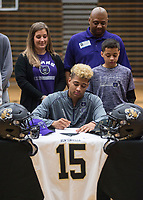 NWA Democrat-Gazette/BEN GOFF @NWABENGOFF<br /> Donte Jones, Bentonville football player, signs his national letter of intent to play at Central Arkansas, with his mother Nikki Jones, father Neal Jones and brother Kobe Jones, 12, looking on Wednesday, Feb. 6, 2019, during a signing ceremony at Bentonville's Tiger Arena.