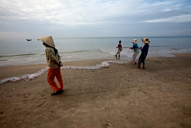 Fishermen haul in a net while a woman walks past on the beach in Mui Ne, Vietnam. Nov. 20, 2011.