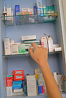 Woman's hand taking medicine from a cupboard fill of prescription drugs and pharmaceuticals.