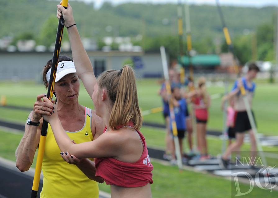 NWA Democrat-Gazette/ANDY SHUPE<br /> April Steiner Bennett (left), a former Arkansas and Olympic pole vaulter, works with camper Madison Sanders, 15, of Marianna, Friday, June 16, 2017, during instruction for pole vaulters at Ramay Junior High School in Fayetteville. Steiner Bennett and Stacy Dragila, a former Olympic pole vaulter and 2000 Olympic gold medalist, were on hand for two days of intensive instruction for vaulters from elementary to high school.