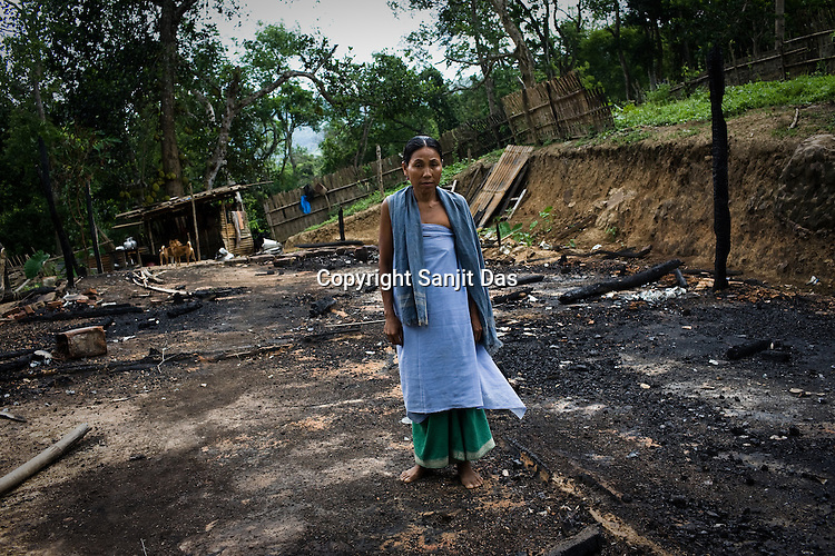 One of the victims of ethnic violence, Joiso Longmalai poses in front of her burnt house in Jorai village. Ethnic clashes are regularly taking place between Zeme Nagas and the Dimasa tribe in North Cachar Hills in Assam, India. On 8th May 200, suspected Zeme Naga groups attacked a Dimasa village and burnt down 10 out of 13 houses. In this act of violence, they spared the school and the community centre, where most of the families are taking shelter.