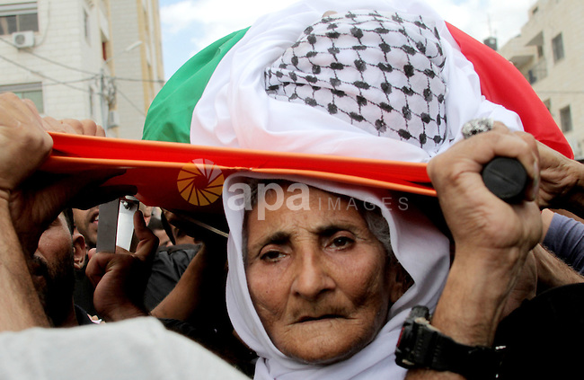 The mother of Palestinian Yassir Hamduni carries his body during the funeral in the west bank village of Yabad, near Jenin City, on September 27, 2016. Hamduni died of a heart condition in Israeli prison on Sunday after years of medical neglect. Photo by Mohammed Turabi