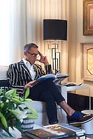 Fashion designer Ben de Lisi reading in his living room