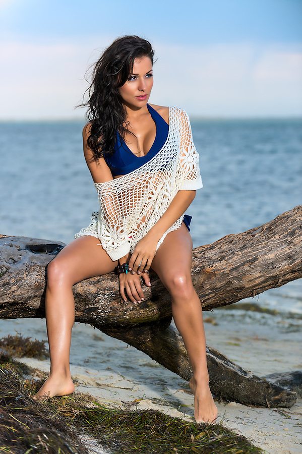 Exotic sexy young woman in a swimsuit and lacy shawl sitting on a branch with her bare legs dangling on a tropical beach against an ocean backdrop