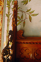 The edge of a carved bed against a hand-painted wall depicting a tree bearing berries