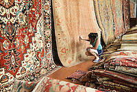 Woman shopping for an oriental carpet.