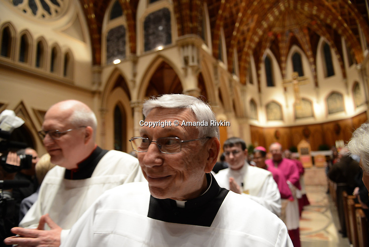 Catholic clergy walk in procession to greet Archbishop-elect Blase Cupich after he ceremoniously knocked on the door of Holy Name Cathedral during the mass ahead of the installation ceremony in Chicago, Illinois on November 18, 2014.  Cupich is the ninth Archbishop of Chicago and succeeds Cardinal Francis George.