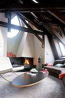 The chalet's living room has a contemporary open fireplace and is furnished with modern designer pieces