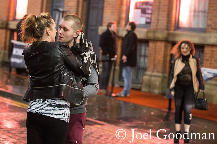 © Joel Goodman - 07973 332324 . 21/12/2013 . Manchester , UK . A couple stand in the middle of a road and kiss . Christmas revellers out in the rain in Manchester on Mad Friday , the last Friday night before Christmas which is typically one of the busiest nights of the year for police and ambulance crews . Photo credit : Joel Goodman