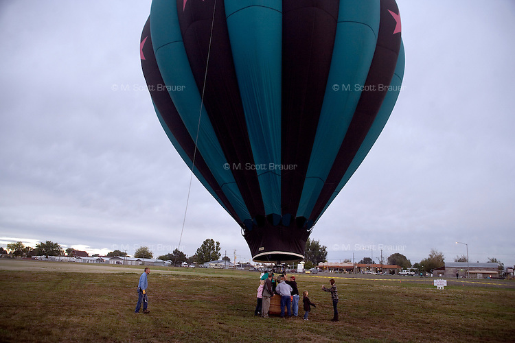 After a light rain started, a hot air balloon returns to the ground and volunteers deflate the balloon at the Great Prosser Balloon Rally in Prosser, Washington, USA.