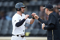Jake Mueller (23) of the Wake Forest Demon Deacons is greeted by teammates after scoring a run against the Sacred Heart Pioneers at David F. Couch Ballpark on February 15, 2019 in  Winston-Salem, North Carolina.  The Demon Deacons defeated the Pioneers 14-1. (Brian Westerholt/Four Seam Images)