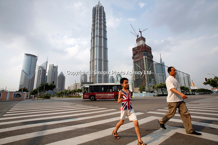 A young boy wearing a British flag t-shirt and his father walks through an intersection near the Jinmao Tower in Shanghai, China..04 Jul 2006