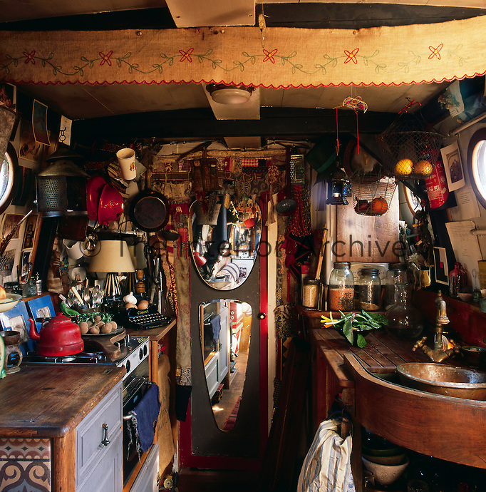 The cosy interior of a canal boat decorated in a bohemian style. The closed mirrored door leads to the sleeping cabin