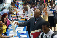 A job seeker offers his resume to a recruiter at a job fair in the East Harlem neighborhood of New York on Wednesday, August 15, 2012.  The job fair is one of the many events occurring during the Harlem Week festivities,  (© Frances M. Roberts)