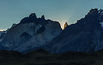 The sun sets behind the Paine Massif with the tip of La Mascara, the Mask, framed by sun rays.  The slope of Monte Almirante Nieto is in the foreground.  The Cuernos or Horns are behind, in front of La Masca.  Torres del Paine National Park in Patagonia, Chile.  A UNESCO World Biosphere Reserve.  Photographed from near the Nordenskjold Overlook.