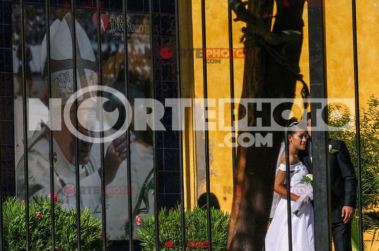 Pareja de novios durante una sesión fotografia en el jardin del aceito Juan Pablo Iim durante el dia de su boda