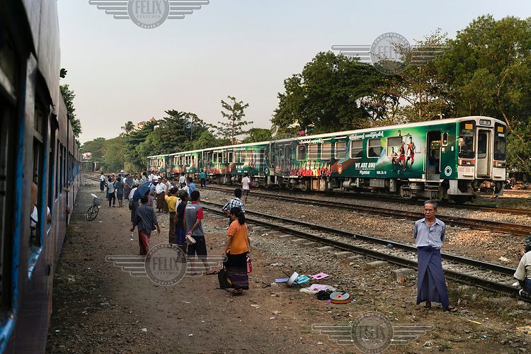 People congregate between tracks as two Yangon Circle Line trains travelling in opposite directions pass each other. Each day, around 100,000 people use the route despite its antiquated rolling stock and infrastructure. The commuter line loops around the city stopping at 38 stations and taking just under three hours to complete the 45 km (28 miles) circle.