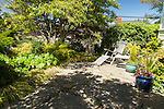 A small flagstone patio surrounded by garden offers a peaceful place to relax.