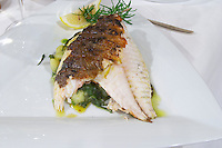 Grilled sea bass with herbs and potato salad on a white plate from the luxury Excelsior Hotel and Spa restaurant terrace Dubrovnik, old city. Dalmatian Coast, Croatia, Europe.