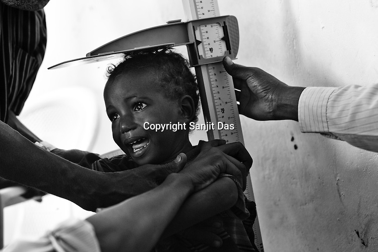 A young child weeps as he is measured for his height at the MSF registration centre in Dagahaley refugee camp in the Dadaab, in northeastern Kenya. Hundreds of thousands of refugees are fleeing lands in Somalia due to severe drought and arriving in what has become the world's largest refugee camp. Photo: Sanjit Das/Panos