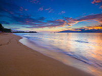 At sunset, waves slowly wash away footprints in the sand along the Ka'anapali Beach shoreline, Maui.