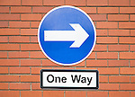 One way road sign with white arrow on blue circle, UK