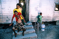 Swinson Nemon, 26, helps his nephew Jason Samuel,14, out of thier home in the North Camp slum. The boy suddenly became paralysed in 2013. Beside them their part-paralysed cousin Jt Nenam, 18, stands with theaid of a walking frame.