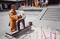 Buddhist monk tending to burning incense in front of a temple at the Yungang Grottoes in Datong, China