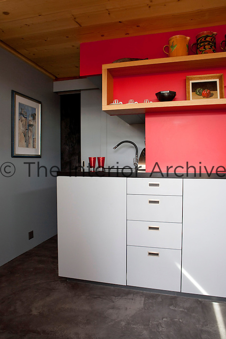 A contemporary kitchen area lines one wall of the living area and is decorated in red and grey