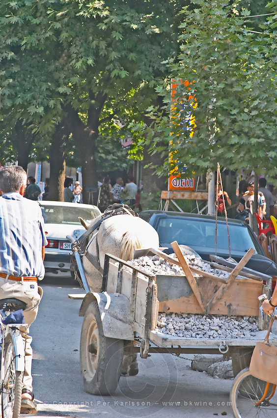 Street scene with a horse drawn cart with gravel on the cart. Shkodra. Albania, Balkan, Europe.