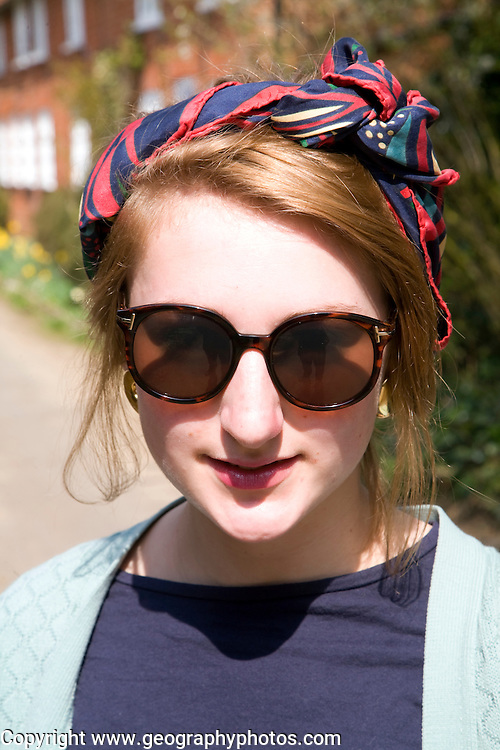 Model released head and shoulders portrait of teenage girl wearing sunglasses and head scarf outdoors