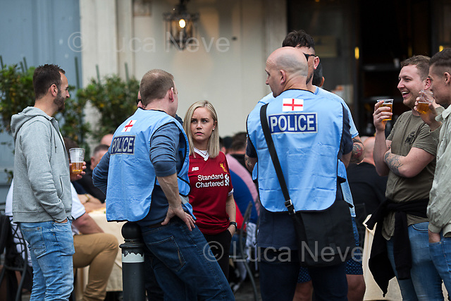 Merseyside Police's officers (British Police).<br /> <br /> Piazza del Popolo.<br /> <br /> Rome, 02/05/2018. Following and documenting a group of Liverpool F.C. supporters chanting and cheering on throughout the streets of central Rome while waiting for the Champions League Semi-final (second leg) at the Stadio Olimpico versus A.S. Roma. The supporters were escorted by heavy presence of the Italian Police and Carabinieri, assisted by Merseyside Police's officers (British Police) and by the stewards and staff from Liverpool Football Club. Last week, during the first leg of the semi-final in Liverpool, an English fan was attacked by Italian supporters outside Anfield stadium. However, the day of the match in Rome passed without any serious incidents involving supporters and just one arrest - a Liverpool supporter - was made (on suspicion of common assault and a public order offence). The actual match was played in the evening and saw Liverpool losing 4-2 but due to the aggregate with the first match, 7-6, the &quot;Reds&quot; conquered the access to the Champions League final in Kiev against Real Madrid. A statement from the English club read: &quot;Liverpool would like to thank all supporters who travelled to Rome for Wednesday evening's Champions League meeting with Roma at Stadio Olimpico for their exemplary conduct. Over 5,000 fans made the journey to the Italian capital for yesterday's semi-final second leg, behaving impeccably throughout, with no major incidents reported. LFC also acknowledges the significant resources deployed by Roma, UEFA, Merseyside police, Italian police and security services in Rome to ensure all fans enjoyed a safe visit.&quot;<br /> <br /> For more info about the football teams please click here: http://www.asroma.com/en &amp; http://www.liverpoolfc.com/