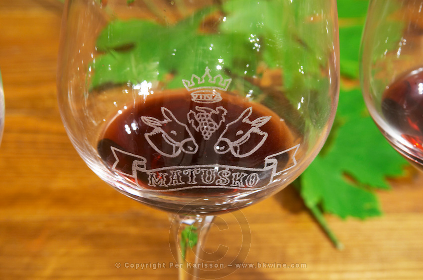 Wine Glass with emblazoned decoration of crown grape bunch two donkey's heads and the winery name. Matusko Winery. Potmje village, Dingac wine region, Peljesac peninsula. Matusko Winery. Dingac village and region. Peljesac peninsula. Dalmatian Coast, Croatia, Europe.