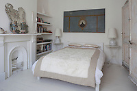A cream fur blanket covers the bed in the white guest bedroom